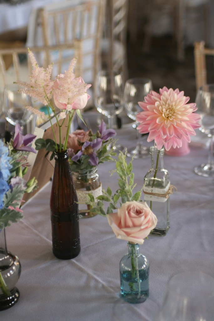 Bottles of blooms for guest tables