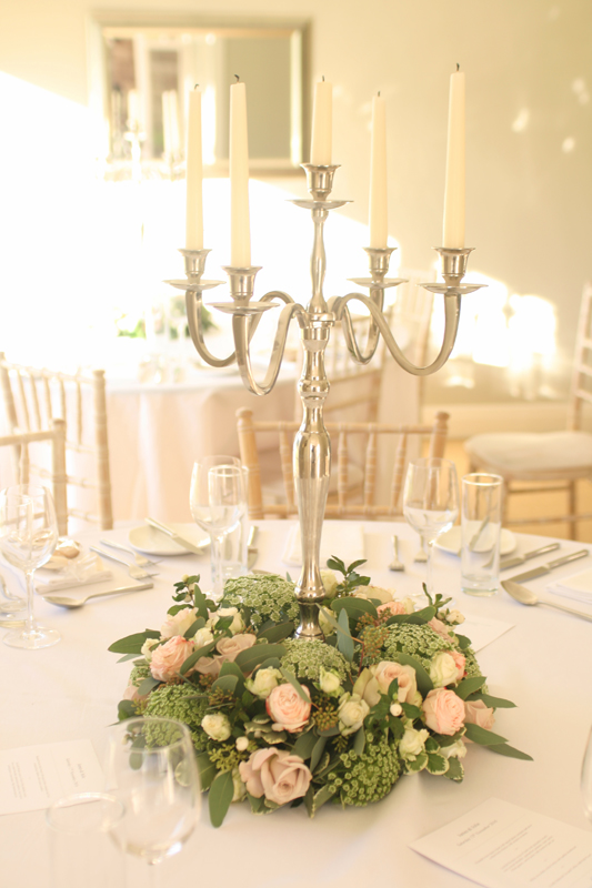 Candelabra centerepieces with a ring of flowers
