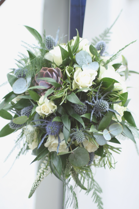 Flower girl pomander with wild foliage and succulents.